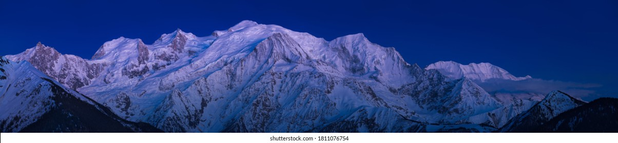 Mont Blanc Massif at twilight with Alpine afterglow. Aiguille du Midi needle, Bossons Glacier, Mont Blanc mountain range. Chamonix, Haute-Savoie (74), Alps, France