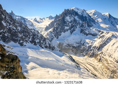 Mont Blanc and the Mer de Glace glacier in the French Alps in winter.  Europe's highest mountain is 4807m high. Warm late afternoon light against a cold blue sky