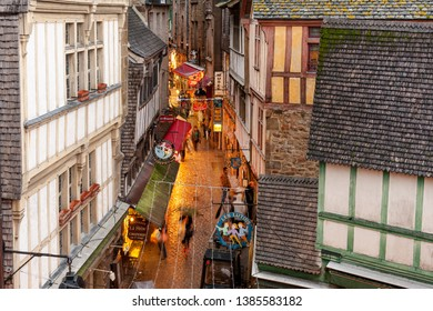 MONT SAINT MICHEL ABBEY, FRANCE- DECEMBER 3, 2011: tourists walking along shops and restaurants on narrow street of the abbey, the most visited place in France.