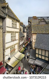 Mont Saint Michel, France - 4/4/2017: Tourists walk in the narrow, medieval Grand Rue in this UNESCO world heritage city.