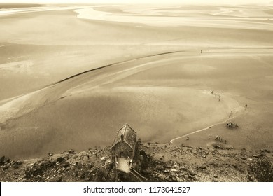 Mont Saint Michel, France. Aerial view of Saint Aubert chapel and groups of tourists walking in the bay during low tide. Sepia photo.
