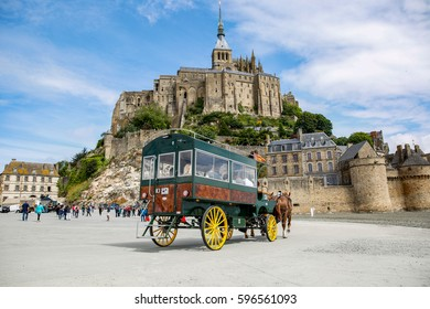 MONT SAINT MICHEL, FRANCE - June 18, 2016: Vintage horse carriage for tourists visiting the popular Mont Saint Michel site in northern France, Normandy