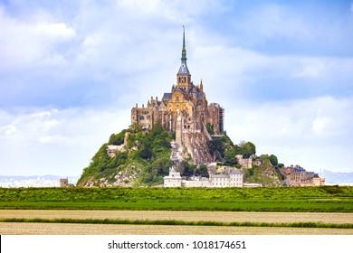 Mont Saint Michel monastery landmark and green field. Unesco heritage site. Normandy, France, Europe.