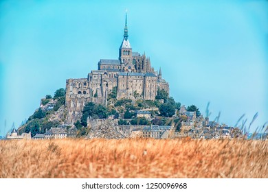 Mont Saint Michel, Normandy France. Medieval city and abbey on the mountain of the same name, surrounded by yellowing and blurred fields.