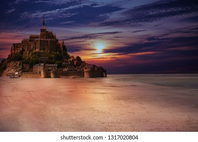 The Mont Saint-Michel with low tide during sunset, Normandy, France. Medieval castle and the abbey on an island, with the sunset blue sky whith clouds.
