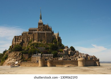 The Mont Saint-Michel with low tide, Normandy, France. Medieval castle and the abbey on an island, with the blue sky and white clouds.