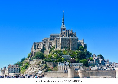Mont Saint-Michel in Normandy  captured during the low tide under a bright, blue summer sky in France.