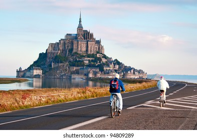 MONT SAINT-MICHEL, NORMANDY, FRANCE - SEPTEMBER 18: Mont Saint-Michel, a rocky island in Normandy, France, is the seat of the Saint-Michel monastery. Two senior people cycling towards the monastery, on Sept 18, 2005.