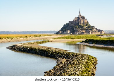 The Mont Saint-Michel tidal island, located in France on the limit between Normandy and Brittany, at high tide with a stone dike on the Couesnon river in the foreground.