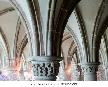 Mont St. Michel, Normandy, France - 9 August 2014: Interior view of church abbey with majestic columns, altar, cross, candleholder and windows.