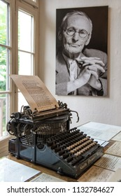 MONTAGNOLA, SWITZERLAND - AUGUST 2012: portrait and original vintage typewriter in Herman Hesse museum in Montagnola, where famous poet and writer 1931–1962 lived. August 2012 Montagnola, Switzerland