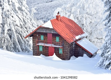 Montain wooden cabin near trees full of snow