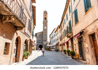 Montalcino, Italy - August 26, 2018: Street in town village in Tuscany during summer day and clock bell tower with people walking and stores in alley