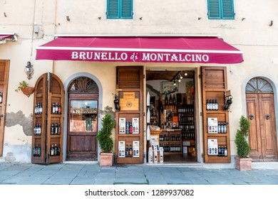 Montalcino, Italy - August 26, 2018: Street in town village in Tuscany during summer day and wine store with many bottles of local drink called Brunello