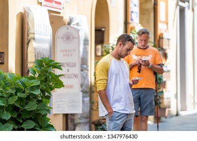 Montalcino, Italy - August 26, 2018: Street in town village in Tuscany during summer day and people walking by stores in alley sale for Brunello wine