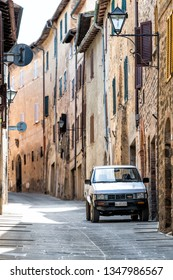 Montalcino, Italy - August 26, 2018: Small historic vertical town stone village with car in Tuscany on sunny summer day and nobody on narrow alley