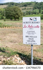 Montalcino, Italy - August 26, 2018: Val D'Orcia countryside in Tuscany with brown soil farm landscape winery vineyard with sign for agriturismo brunello wine