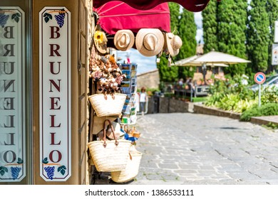 Montalcino, Italy - August 26, 2018: Street in town village in Tuscany during summer day and wine store with sign for Brunello local drink