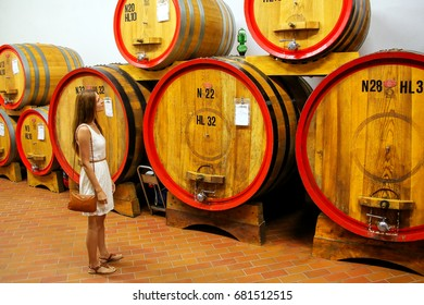 MONTALCINO, ITALY - MAY 19: Uniedntified woman stands next to wooden barrels in a wine cellar on May 19, 2015 in Montalcino, Tuscany, Italy. The town is famous for its Brunello di Montalcino wine.