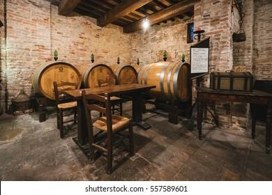 Montalcino, Italy - November 1, 2016: Oak barrels in an old Italian wine cellar.