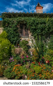 MONTALCINO, ITALY - OCTOBER 4, 2019: Montalcino, Tuscany, a hilltop town in the splendid Val d'Orcia.  In this photo there is a beautiful house with ivy and flowers
