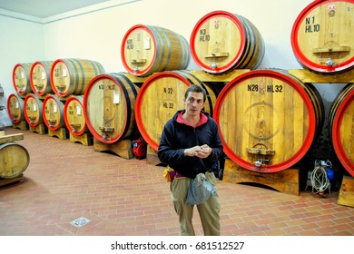 MONTALCINO, ITALY-MAY 13: Unidentified man stands next to wooden barrels at his winery on May13, 2014 near Montalcino, Tuscany, Italy. The town is famous for its Brunello di Montalcino wine