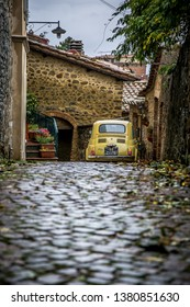 MONTALCINO, TUSCANY/ITALY - 28 OCTOBER 2018: Street of the ancient town of Montalcino in Tuscany. Fiat 500 parked in an alley. Tuscany, Italy