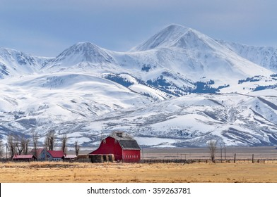 Montana farm dwarfed by tall mountains.