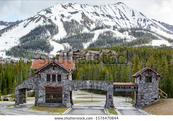 Montana, USA 2011;Moonlight basin archway gate entrance against pine trees and mountains.  Moonlight Basin is a ski resort in the Madison Range of the Rocky Mountains in the resort village of Big Sky.