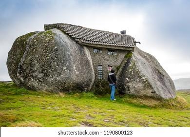 "Montanas de Fafe, Portugal- December 27 2010: ""Casa do Penedo"" also known as ""The Fafe Hobbit house"" is a tiny residential home, built between big solid rocks in Montanas de Fafe, Portugal"