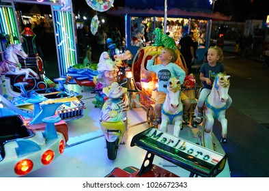 MONTANYAN, ITALY - 16 JULY 2017: Children's amusement rides. late at night children have fun
