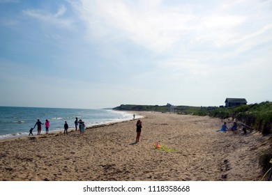 MONTAUK, NEW YORK-JUNE 8: Beachgoers and girl seen flying kite on Ditch Plains Beach, Montauk, The Hamptons, New York on June 8, 2018.