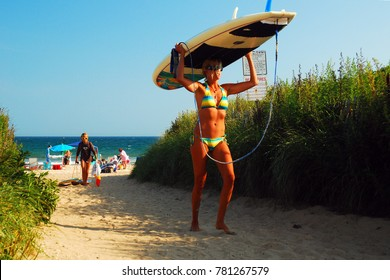 Montauk, NY, USA July 27, 2010 A young woman carriers her surfboard from Ditch Plains Beach in Montauk, New York.  Ditch Plains is considered one of the premier surfing locations on the east coast
