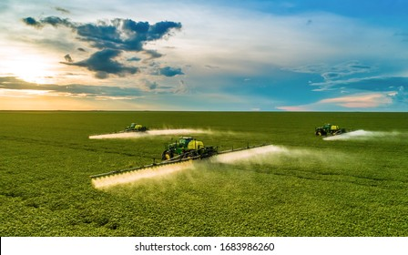 Monte Alegre de Minas, Minas Gerais, Brazil, February 27, 2020: Agricultural sprayers making application at the end of the day with beautiful sunset, blue sky with clouds