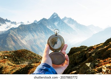 Monte Bianco mountains range and tourist hand with old metal compass on a foreground. Vallon de Berard Nature Preserve, Chamonix, Graian Alps. Travel concept. Landscape photography