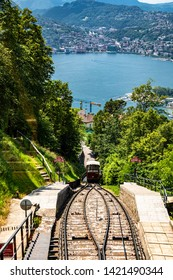 Monte Bre, Switzerland - June 08, 2019 View of the Mont Bre funicular going down with lake Lugano at the background