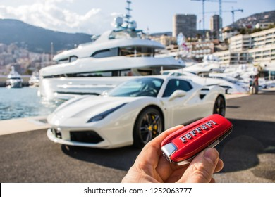 Monte Carlo, Monaco 7 December 2018, Ferrari 458 Italia Spider 2019 white, stands on parking by yachts and men hand hold Ferrari key