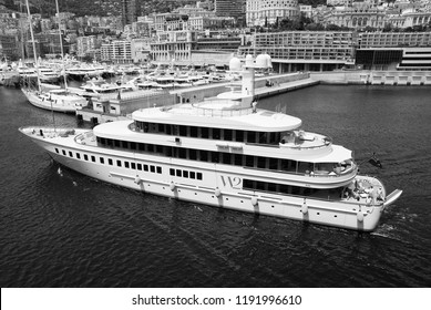 Monte Carlo, Monaco - December 08, 2009: W2 Wedge Too yacht in sea harbor. Yacht club and city houses on mountain landscape. Sea adventure and summer boat trips. Pleasure and sport. Vacation and
