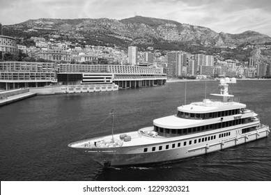 Monte Carlo, Monaco - December 08, 2009: W2 Wedge Too yacht go along sea coast. Water craft and city on mountain landscape. Luxury lifestyle. Pleasure and sport. Summer vacation and wanderlust.