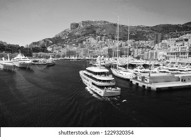 Monte Carlo, Monaco - December 08, 2009: yacht Wedge Too W2 go into sea harbor with houses on mountain landscape. Yacht club and city on summer seaside. Sea adventure and boat trips. Vacation