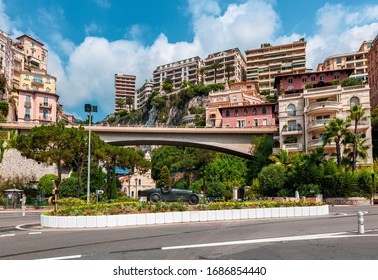 MONTE CARLO, MONACO - JULY 13, 2013: Colorful buildings and bridge behind sculpture of William Grover-Williams in Bugatti racing car- the first winner of Monaco Grand Prix on April 14, 1929.