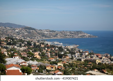 Monte Carlo, Monaco - September 21, 2015: city coastline by sea beach residential buildings on mountain hills on blue skyline on seascape background