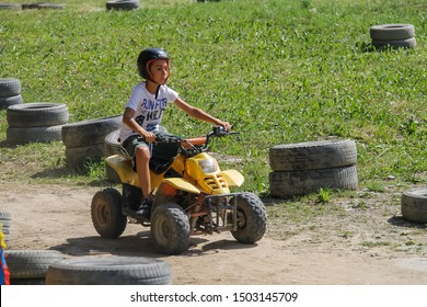 Monte Cimone, Italy - July 31, 2016: Teen boy drives a quad bike on slope of Monte Cimone mountain