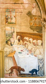 Monte Oliveto Maggiore, Italy - August 6, 2018: Fresco in the Monastry of Monte Oliveto Maggiore, near Siena, Tuscany, Italy, depicting Saint Benedict feeding the monks.
