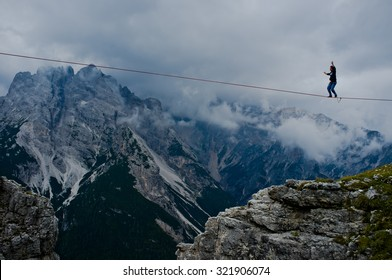 """MONTE PIANA, DOLOMITES/ITALY - SEPTEMBER 08, 2013: an acrobat on a rope tended above an abyss during """"Highline Meeting"""" of tightrope walkers from around the world taking place every year on september"""