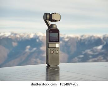 MONTE PORA, ITALY - 10 FEBRUARY, 2019. Dji Osmo pocket gimbal. Alps mountain range in the background