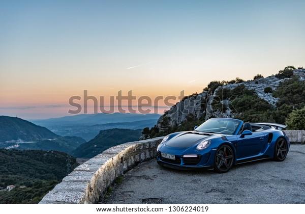 Monte-Carlo, Monaco 6 February 2019, Porsche 911 Turbo S Cabriolet blue open roof, sunset mood in mountain
