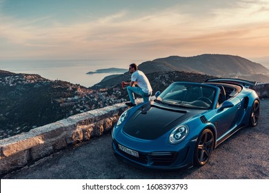 Monte-Carlo, Monaco 7 January 2020, Porsche 911 Turbo S Cabriolet Stinger tuning blue with open roof, Man chilling and relaxing, background sunset mood in mountain with sea panorama.