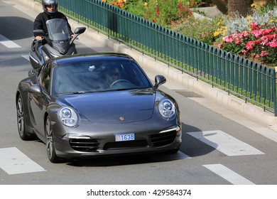 Monte-Carlo, Monaco - May 18, 2016: Beautiful Woman Driving an Expensive Porsche 911 Carrera S on Avenue Princesse Grace in Monte-Carlo, Monaco in the south of France
