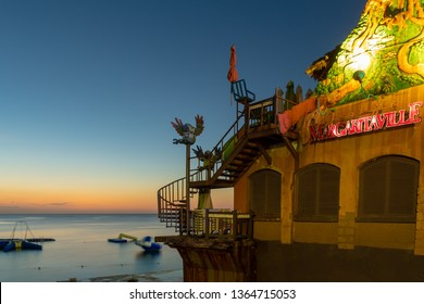 Montego Bay, Jamaica - April 06 2019: Beautiful sunset twilight glow/ afterglow behind water trampolines on the ocean at Margaritaville Montego Bay Jamaica on Jimmy Cliff Boulevard aka the Hip Strip.
